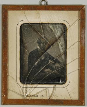 Mann mit Bart am Tisch seitlich sitzend, einen Arm abgestützt, Halbfigur.
