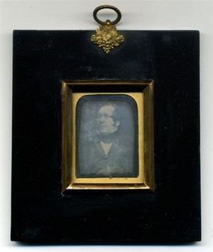 conservation done. Wood frame with gold hanger decorated with flowers and leaves. Might be the husband portrait of F39934