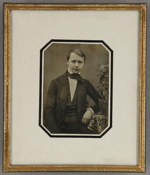 Junger Mann an einem Tisch mit Blumengesteck sitzend, Halbfigur.