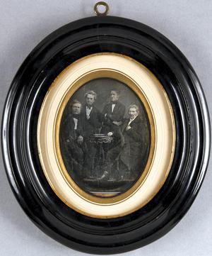 Vier ältere Herren um einen kleinen runden Tisch sitzend und stehend, Ganzfigur.