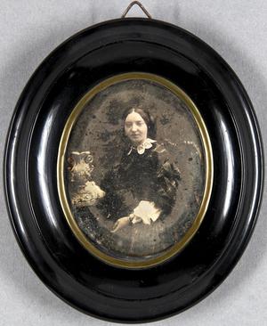 Junge Frau in einem Sessel an einem Tisch mit Porzellanvase sitzend.