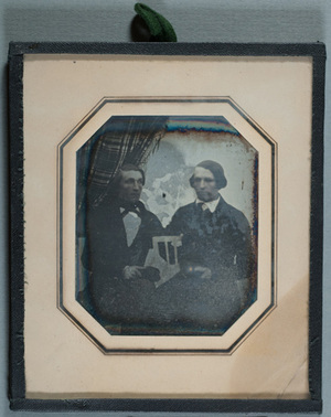 Portrait of the Levón brothers, checkered textile on the background.