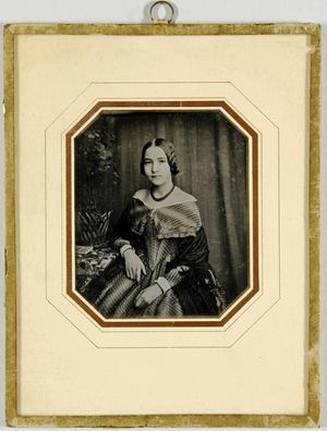 Junge Frau am Tisch mit einem Blumengesteck sitzend, einen Arm darauf abgestützt, im Hintergrund ein drapierter Vorhang.