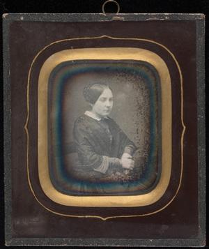 Portrett av kvinne med oppsatt hår sittende på stol. Arm lenes på bord. Lousie J. J. Mathiesen, født Larpent 1835-1875.  Portrait of woman with an interesting hairstyle. Arm leaning on table. Lousie J. J. Mathiesen, born Larpent 1835-1875