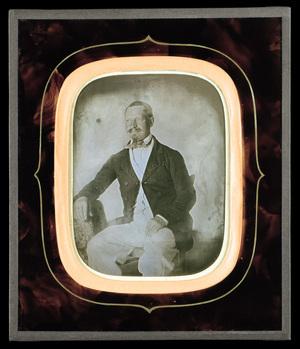 Portrait d'un homme moustachu assis.