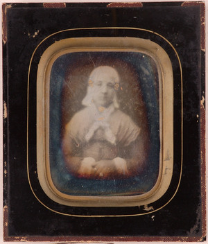Portrait of an unknown woman with hood, seated with crossed hands