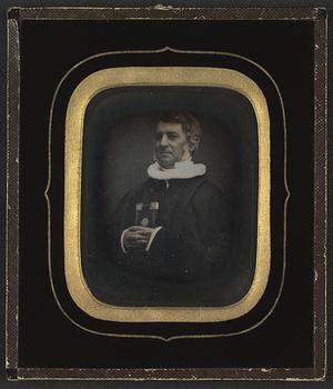 Portrett av en eldre luthersk prest med en bok med pokostet innbinding Portrait of an elderly lutheran priest holding a richly bound book in his hands.