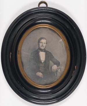 Portrett av en sittende mann med bart som lener seg mot et bord med en mønstrete duk.  Portrait of a seated man with moustache leaning against at table with a patterned tablecloth.