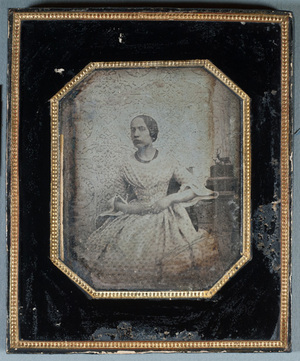 Portrait of a young woman, pattern in a back drop, small statues on a side.