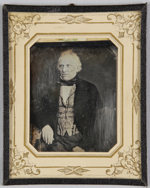 Älterer Mann mit gemusterter Weste an einem Tisch sitzend, einen Arm darauf ruhend, Halbfigur.