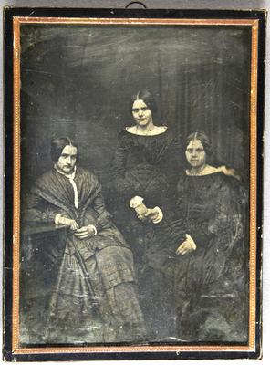 Drei Frauen in dunkler Kleidung vor dunklem Hintergrund sitzend und stehend.