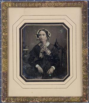Ältere Frau mit Spitzenkragen und -haube und kariertem Schal sitzt am Tisch mit einem Blumengesteck, einen Arm abgestützt, Halbfigur, koloriert.