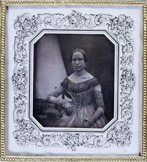 Portrait of unknown woman in a striped dress, signed by Carl Neupert. Muotokuvassa nainen raidallisessa pitsikauluksisessa hameessa, suuret korvakorut ja useita sormuksia. Oikeassa alakulmassa tekijän signeeraus, raaputettu kuvalevyn pintaan.