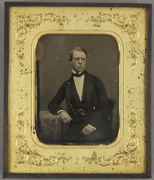 Junger Mann an einem Tisch sitzend, ein Arm darauf abgestützt.