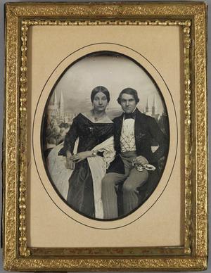 Ehepaar sitzend, sie mit weißem langem Schal, er mit karierter Weste vor gemalter Kulisse mit der Lübecker Marienkirche und dem Dom