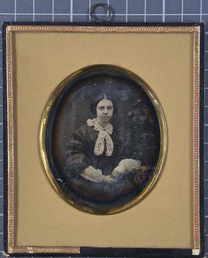 Junge Frau mit Spitzenkragen sitzt an einem Tisch mit Blumenschmuck, einen Arm abgestützt, Halbfigur.