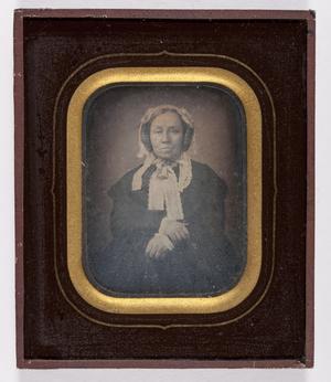 Oudere vrouw, haar opgekruld op de oren, zittend, draagt een  zwarte jurk , witte kapmuts met linten en broche