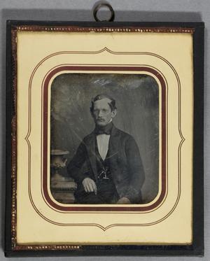 Mann mit Schnurrbart und Brille neben einem Tisch mit Vase sitzend, Halbfigur.