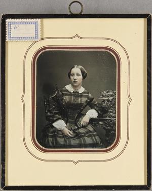 Junges Mädchen in kariertem Kleid, mit weißem Kragen, am Tisch mit einer Blumenvase sitzend, Dreiviertel, koloriert.