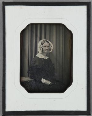 Ältere Frau mit weißer Haube seitlich neben einem Tisch sitzend vor einem Vorhang im Hintergrund.