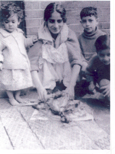 photograph: [Mrs Mumtaz Khalique plucking a chicken watched by Robeena, Javed and Parvaze]