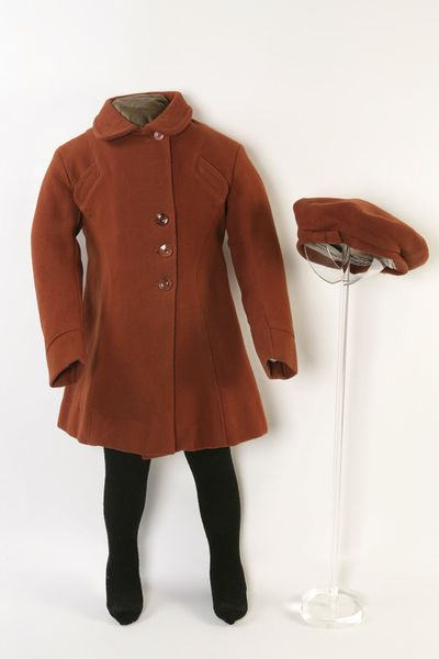 Girl's coat and hat of russet wool, made in England under the Utility scheme 1941-1948. Girl's coat and matching hat of russet wool. Coat of russet-coloured wool lined with grey rayon.  It is cut in a flared, single-breasted style, with three buttons (the maximum allowed under the Utility scheme) just to one side of centre, and an additional button beneath the Peter Pan collar.  The coat front is cut in four panels, the two central ones being rever shaped, with saddle stitched top flaps to match the stitching on the collar.  The back of the coat is cut in three panels, with an inverted pleat at the centre back of the skirt, and a half-belt of self fabric.  The coat has a hanging bar of the lining fabric inside the neck. Beret shaped hat of russet-coloured wool lined with grey rayon, to match the coat.  It has a saddle-stitched hat band, trimmed with a bow of self fabric at the centre front.Wool lined with rayon.