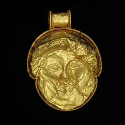 Pendant, gold, depicting a mask, northern Italy (Tuscany or Umbria), Etruscan, 5th-3rd century BC. Pendant, gold, decorated with mask depicting the face of a bearded man, perhaps a deity.  Gold.