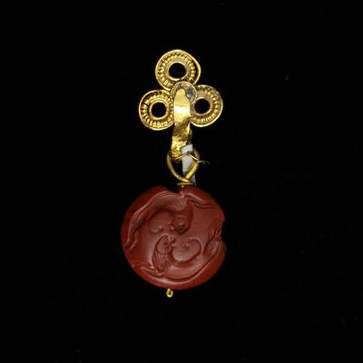 Pendant, gold hung with a lenticular gem of red jasper engraved with two lions, Greece, Mycenaean period, about 1450-1100 BC. Gold pendant hung with a lenticular gem of red jasper engraved with two lions.  Gold hung with engraved red jasper.