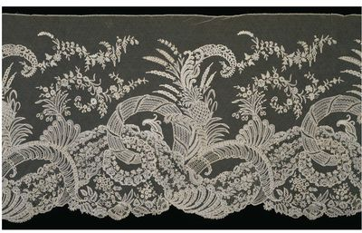 Deep flounce of appliqué lace, Brussels, ca.1860.Deep flounce of high quality lace with complex pattern of floral and plant forms including pineapples.Bobbin and needle lace appliqué on machine-made net.