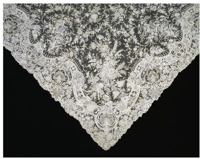 Veil of point de gaze needle lace, Brussels, 1890-1.Wedding veil of high quality Point de Gaze needle lace with a hand-made réseau, fine shading effects and a large variety of decorative filling stitches. In the centre of the veil is a bouquet of flowers enclosed by an eight-point star composed of floral garlands. Further sprays fill the points of the star and also the ground between the centre-piece and the elaborate border. At each corner are larger elaborate, densely worked sprays which extend to the centre of the veil. The border is formed by a solid, serpentine line, broken at intervals by sprays of flowers and by elaborately-patterned cartouches. The filling stitches used are clear-cut, solidly-worked and very varied. The effect of the border is three-dimensional and architectural. The area between the serpentine line and the scalloped edge is filled with naturalistic flower forms.Needle lace.