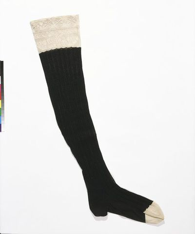 Machine-knitted silk stocking, made by Pope & Plante, London, 1851.Stocking of black and white machine-knitted silk. The main part of the stocking is black with the toe and top in white. The black part of the stocking is knitted in a fancy rib and there is a plain foot. It is shaped to the calf, but not fashioned. There is a seam at the bottom of the foot and the toe, which is squared off and fashioned, and the heel is knitted in heavier quality silk. Knitted into the white silk welt is a series of openwork triangles and below them are knitted the words 'POPE & PLANTE 1851 BY INDUSTRY WE THRIVE' with decorative filling.Machine-knitted silk.
