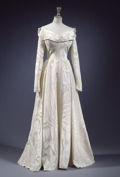 Wedding dress in cream silk moir with a full length, full skirt, closely fitted bodice and long tight sleeves. The  neckline cut wide and low, with a knife-pleated bertha collar. Row of closely spaced covered buttons at wrists and  back zipper. Two stiffened synthetic silk waist-petticoats, the top one in silk with a deep moir flounce, the bottom  a crinoline slip interlined with stiffening to support the skirt. Wedding veil of fine silk net attached to a cream satin  band with elastic band. Matching cream silk moir sandals, made by Rayne, with wrap-over effect peep-toe and  button, low-ish heel and ankle straps.