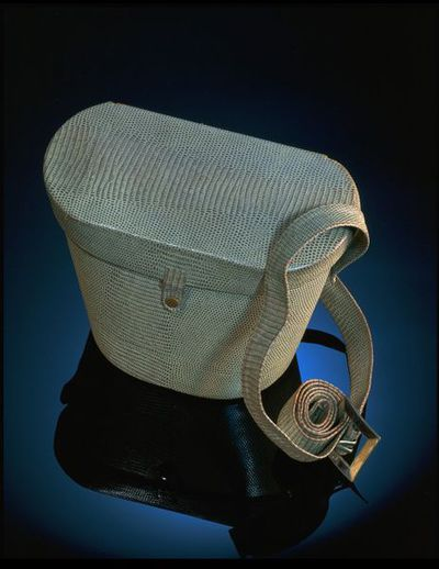 Reptile skin gas-mask bag with gas mask inside, H Wald & Co., Great Britain, 1940-1942. Light tan reptile skin gas-mask bag with a top closure and long strap with buckle. Containing a gas mask.Reptile skin.