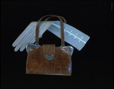 Pair of doeskin gloves with wrapping tissue paper, made by Reynier, France, ca. 1900.Pair of pale blue doeskin gloves, forearm length, with four mother of pearl buttons up the forearm. The button holes, the wrist opening and cuffs are piped with white. There are three self stitched lined on the back. With the original wrapping paper made from white tissue paper marked 'Best quality kid and suede'.Doeskin, mother of pearl, tissue paper.