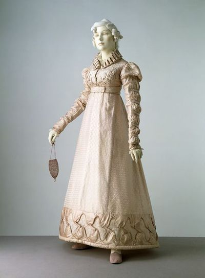 Dress and spencer jacket made from silk, England, ca. 1823.Dress and spencer jacket made from pink silk with a figures leaf design.  The dress has a low rounded neckline, and a high-waisted bodice fastened at the back with an attached belt. The skirt is gored, though the whole breadths are not cut away, and is pleated at the centre of the back. The matching jacket has a turned down collar and long sleeves arranged in puffs which diminish slightly towards the wrist. It has an attached belt trimmed with loops and a silk waist ribbon. Bodice and jacket are lined with silk. The dress is remarkable for the quality and variety of its faced and applied decoration. There are faced slits which stiffen the collar, leaf shapes on the jacket, petal shapes on the bodice and a deep scalloped satin border with a padded hem.  The matching jacket would make the dress suitable for less formal occasions.Figured silk, trimmed with silk, lined with silk, hand-sewn.