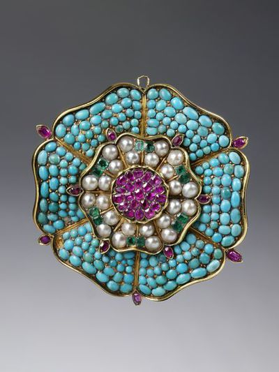Brooch in the form of a Tudor rose, gold, pavé-set with turquoises, rubies, emeralds and pearls, probably made in England, 1830-40.Ornament in the form of a Tudor rose, gold, pavé-set with turquoises, rubies, emeralds and pearls. Originally the centre ornament from a bracelet that has been altered into a brooch. Fitted with a locket back.Gold, pavé-set with turquoises, rubies, emeralds and pearls.