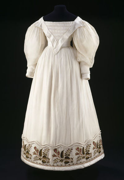 Dress of muslin embroidered with stylized rosebuds and foxgloves. Trimmed with silk satin and wadded rouleaux, Great Britain, France, ca. 1830.Dress of muslin embroidered with stylized rosebuds and foxgloves. Trimmed with silk satin and wadded rouleaux.Cotton muslin with wool embroidery, silk satin and wadded rouleaux.