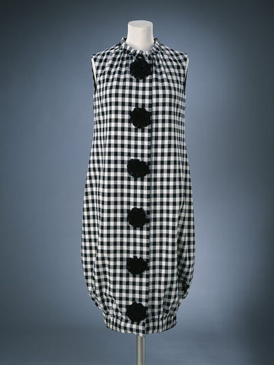 Ensemble, F, 1956-7, English; Quant, Mary. Black and white check wool. 1973 replica. ensemble, F, 1956-7, English; Quant, Mary. 1973 replica. ensemble, F, 1956-7, English; Quant, Mary. Black leather. 1973 replica.Black and white check dress with black rosette pom poms to front.Wool.