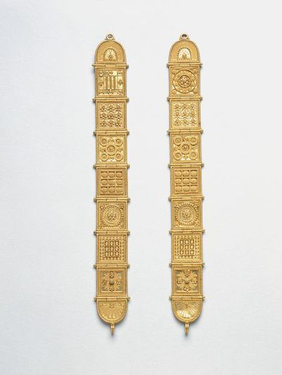 Hinged bracelet, gold with filigree and granulation, made by Castellani, Italy, about 1860-80. Etruscan-style bracelet with hinged panels. Applied wire and granulated decoration. Signed with the monogram 'AC' in applied wire, for Alessandro Castellani. Design adapted from 'ancient' bracelets, part of the Campana collection now in the Louvre, Paris. The Louvre bracelets are made of authentic Etruscan a baule earrings of about 600-450 BC hammered flat mixed with modern plaques in the Etruscan style, made into a bracelet in the second half of the nineteenth century.  Gold, hinged panels with applied wire and granulated decoration.