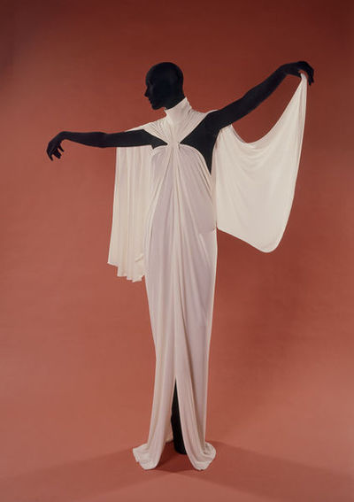 Draped rayon jersey evening dress, designed by Yuki, London, 1976. Draped white rayon jersey evening dress, backless halter neck style. Heavy white jersey full length evening dress suspended from a choker neckline to create a body-skimming draped backless column of fabric, hanging drapes from collar over each shoulder.Knitted rayon jersey.
