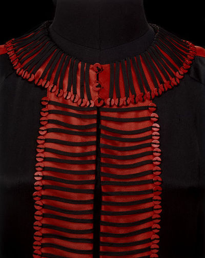 Day dress and belt of black satin, made in Germany, 1920s. Day dress and belt of black satin. Dress with red ribbon trimming. With wooden buttons and numerous parallel rows of wool braid to create a bold, purely decorative pattern on this black satin overdress. The repetition of this tiny detail creates an arresting geometric pattern, achieving an almost military look.Satin and rayon trimmed with wool braid, and with wooden buttons.