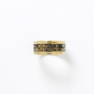 Gold and enamel mourning ring commemorating the deaths of seven children, England, 1801. Gold band enamelled in black with narrow white enamel border at top and bottom. The outside of the hoop is inscribed in reserve on the black enamel: 'MB Agd 16 SB Agd 12 WB Agd 10 EB Agd 9 TB Agd 7 RB Agd 5 CB Agd 2'. The inside of the hoop is engraved with an inscription in italics: 'Died from the 16th to the 23rd Feby. 1801'.  Enamelled gold.