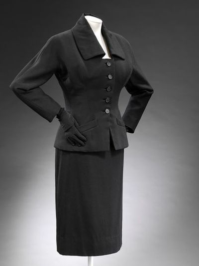 Wool jacket and skirt suit with silk lining, designed by Christian Dior London Ltd., London, 1954. Black wool jacket and skirt suit with silk lining. Fitted jacket with a low neckline and sculptural collar. Single breasted and with 5 buttons down the front. Welted pockets on peplum. Slim skirt.Wool with silk lining.