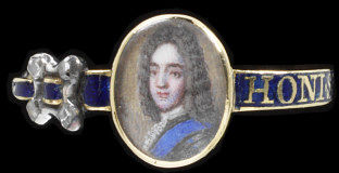 Gold and blue enamel ring in the form of a garter set with a miniature portrait. English, 1730-70. Hoop imitating a garter, the bezel in the form of a small oval portrait miniature of a man. To the left of the bezel, an imitation buckle set with four diamond chips and a strap terminating in a diamond chip. The hoop is enamelled in royal blue with an inscription in reserve capital letters reading HONI SOIT QUI MAL Y PENSE.  Enamelled gold, set with diamonds and a miniature painting under rock crystal.