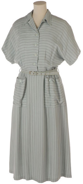 Day dress and belt, blue rayon with maroon vertical stripe, 1942-1945, London; Norman Hartnell for Berketex. Pale blue rayon day dress with a fine maroon banded vertical stripe. The dress is a shirt waist with cap sleeves in one with the bodice. It has a straight skirt, slightly gathered over each button, a fastened patch pocket and an inverted pleat at the centre back of the skirt. It fastens with a hook at the placket and has a self covered belt with a brass metal buckle.Rayon, brass.