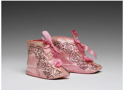 Pink satin baby's boots with couched silver thread decoration, English, 1800-1830.Pink satin baby's boot with cream wool lining and leather sole. Pink silk ribbon laces in 4 pairs of lace holes with a small pink rosette just below the bottom pair. Couched silver thread decoration in the form of a scrolling foliate motif which stretches from toe back to top of boot.Silk satin with couched silver thread, wool lining, leather, silk ribbons.