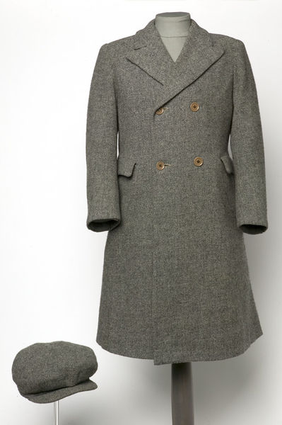 Boy's coat and cap; English, 1930s. Boy's grey tweed coat and cap; Boy's tailored double-breasted coat of grey tweed lined with grey rayon.  The coat has a turn-down collar with notched lapels, wrist-length sleeves, and inset pockets (with self fabric flaps) at the waist; the skirt back is cut with a central box pleat beneath a half-belt of self fabric.  The garment fastens across the chest front with two pairs of buttons and stitched buttonholes, and has a hanging loop of lining fabric in the neck. Matching eight-gore peaked cap, the cap fastening to the peak with a metal press stud at the centre front.Tailored tweed with a rayon lining.