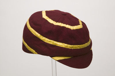 Boy's school cap of maroon wool; England, 1900-1920. Boy's eight-gored school cap of maroon wool lined with cream coloured cotton.  The cap is ornamented with hand stitched concentric circles of yellow cotton tape, with part of a band across the peak, and is finished with a bound button at the crown.Wool and cotton, machine stitched and hand stitched.