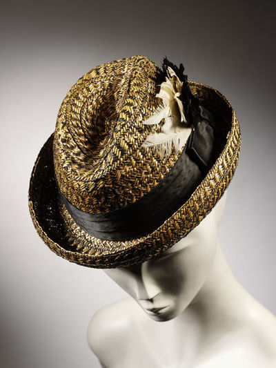 Man's hat of straw, pork pie shape, Great Britain, ca. 1898.Straw hat of black and white split straw plait. It is of pork pie shape with black satin band and black and white feather cockade. It is lined with white rayon. The lining may be more recent.Woven straw, satin, feathers and rayon lining.