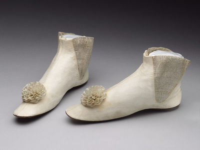 Pair of wedding boots with kid upper, elasticated inner side gusset, silk rosette and cork insoles, Britain, 1865.Each boot has a cork insole inserted inside probably to help keep out the damp. One of the insoles is inscribed: 'Superior Quality Cork Soles'.Kid upper, with elasticated inner side gusset and silk rosette.